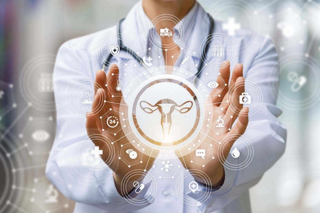 The doctor shows the icon of the female uterus on blurred background.
